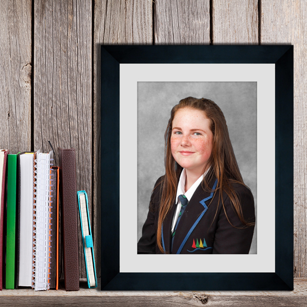 Portrait school photograph in a black frame and grey card mount displayed on a wooden shelf