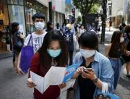 Tourists wearing masks to prevent contracting Middle East Respiratory Syndrome (MERS) look at a tour map of Seoul at Myeongdong shopping district, in central Seoul
