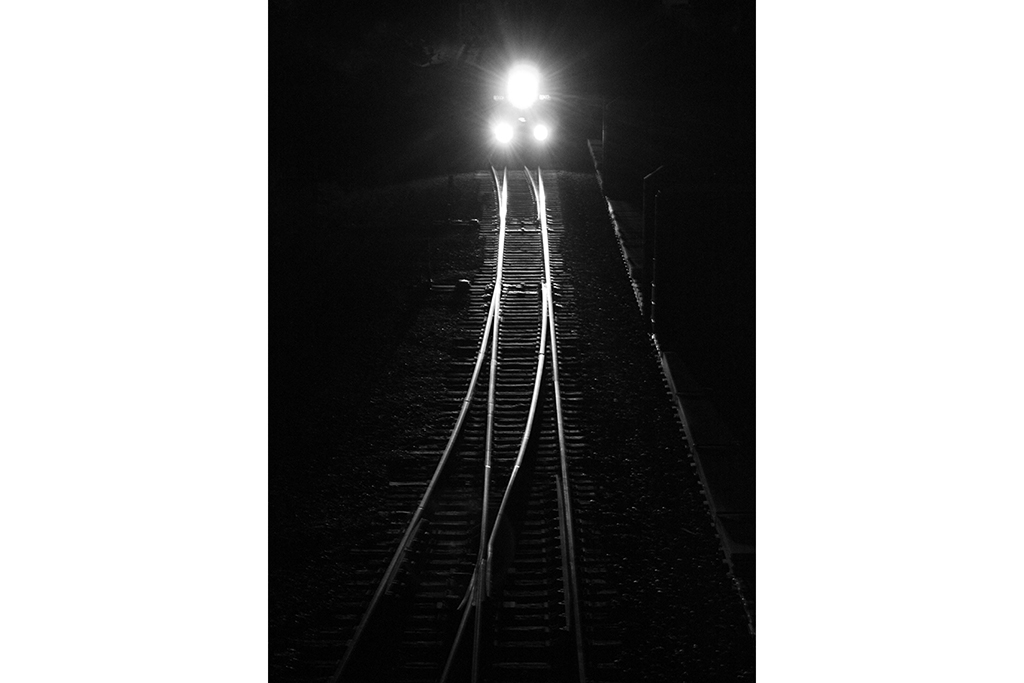 locomotive headlights illuminating rails at night