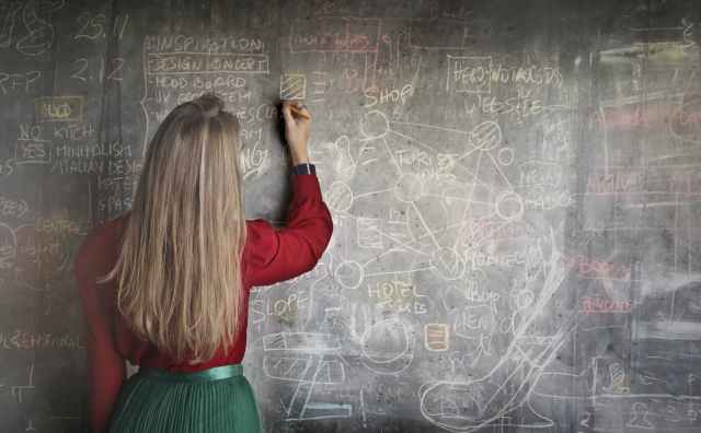 Earn $10,000 Per Month Online, Using What You Already Know - woman sitting on brown wooden chair while using silver laptop computer in room  - woman in red long sleeve writing on chalk board