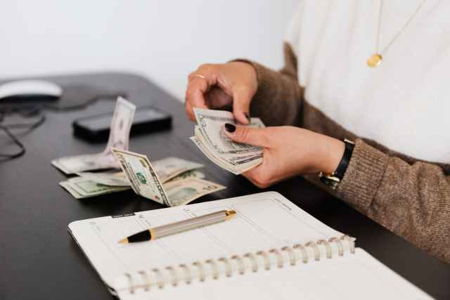 crop payroll clerk counting money while sitting at table