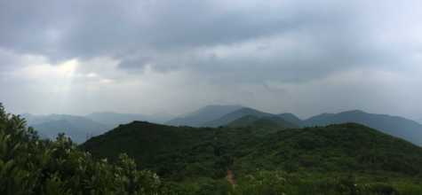 """On his hike, Manson Tung saw Hong Kong Island shrouded in clouds with Jesus Light in the upper left corner. Beyond the mountains, he said, is Central, """"the beating heart of Hong Kong."""""""