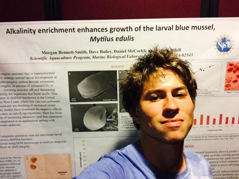 Bennett-Smith stands in front of his Research Symposium poster. His project focused on measuring larval bivalve growth in various chemically-manipulated seawater treatments.