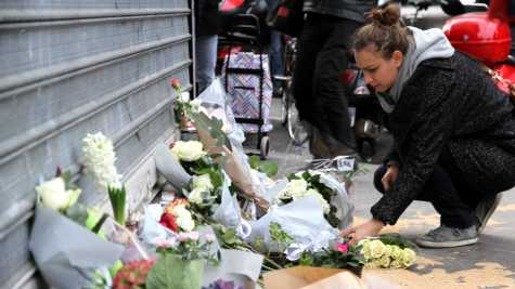 A woman mourns the losses of the hundreds killed in the recent Paris attacks.