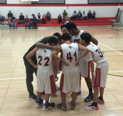 The JV boys huddle around coach Gary Brisco.