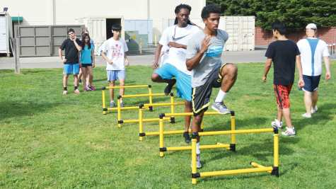 To stretch their hamstrings and calves, senior Serajh Esmail, junior Jaelan Trapp, sophomore Steven Wang, freshman Kyra LaFitte and seventh grader Cash Taylor do high knees over hurdles during a track and field practice.