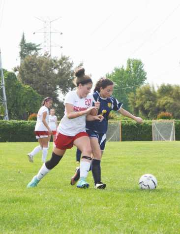 Freshman Abby LaComb (20) tries to break away from a Wolf.