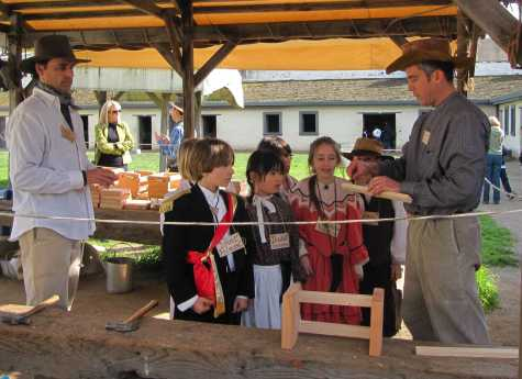 Terry Harvago, father of former middle-school student Hank and current eighth grader Charlie, and Andrew Sackheim, father of sophomore Benett, teach fourth graders to make and brand wooden boxes at a station in Sutter's Fort.