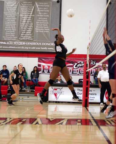 Freshman Monet Cook hits a ball as sophomore Lia Kaufman runs behind ready to assist.