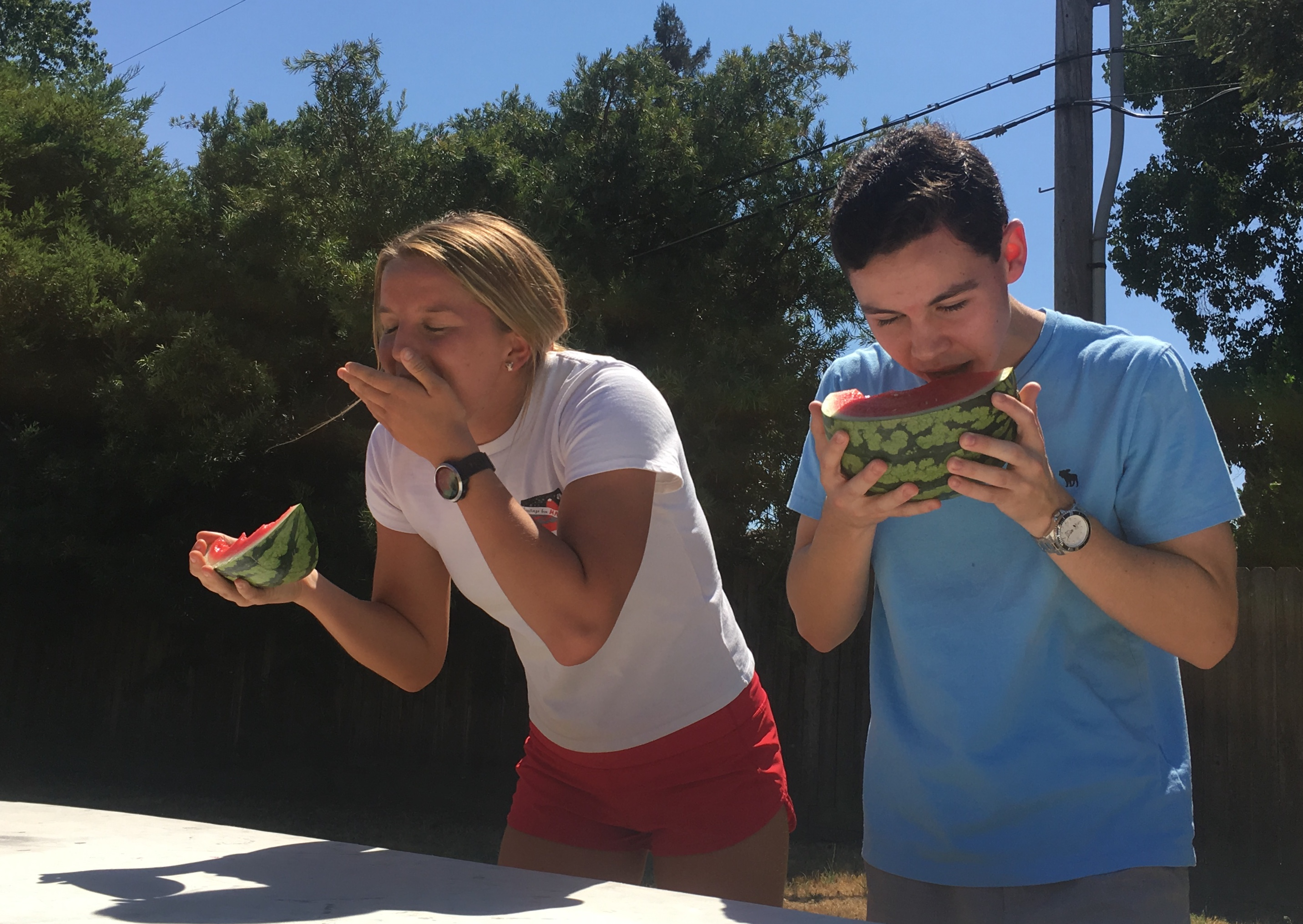 Junior Sydney Turner tries not to choke on her watermelon as she and sophomore Craig Bolman quickly consume the fruit. (Photo by Héloïse Schep)