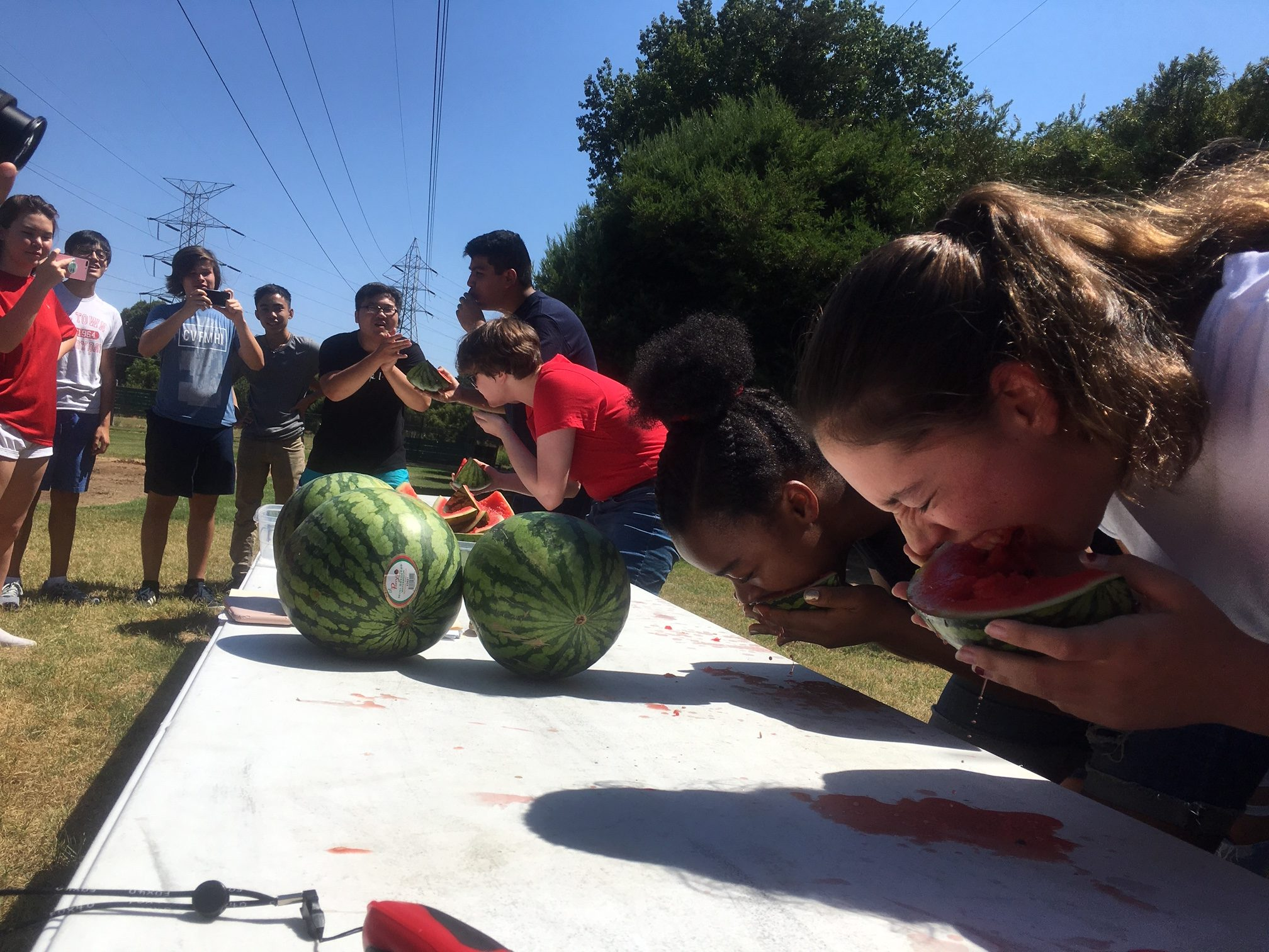 Racing against juniors Michael Tovar (fourth from right) and Anna Fluetsch (third from right), freshmen Emily Cook (far right) and Savanna Karmue devour their watermelon slices. (Photo by Larkin Barnard-Bahn)