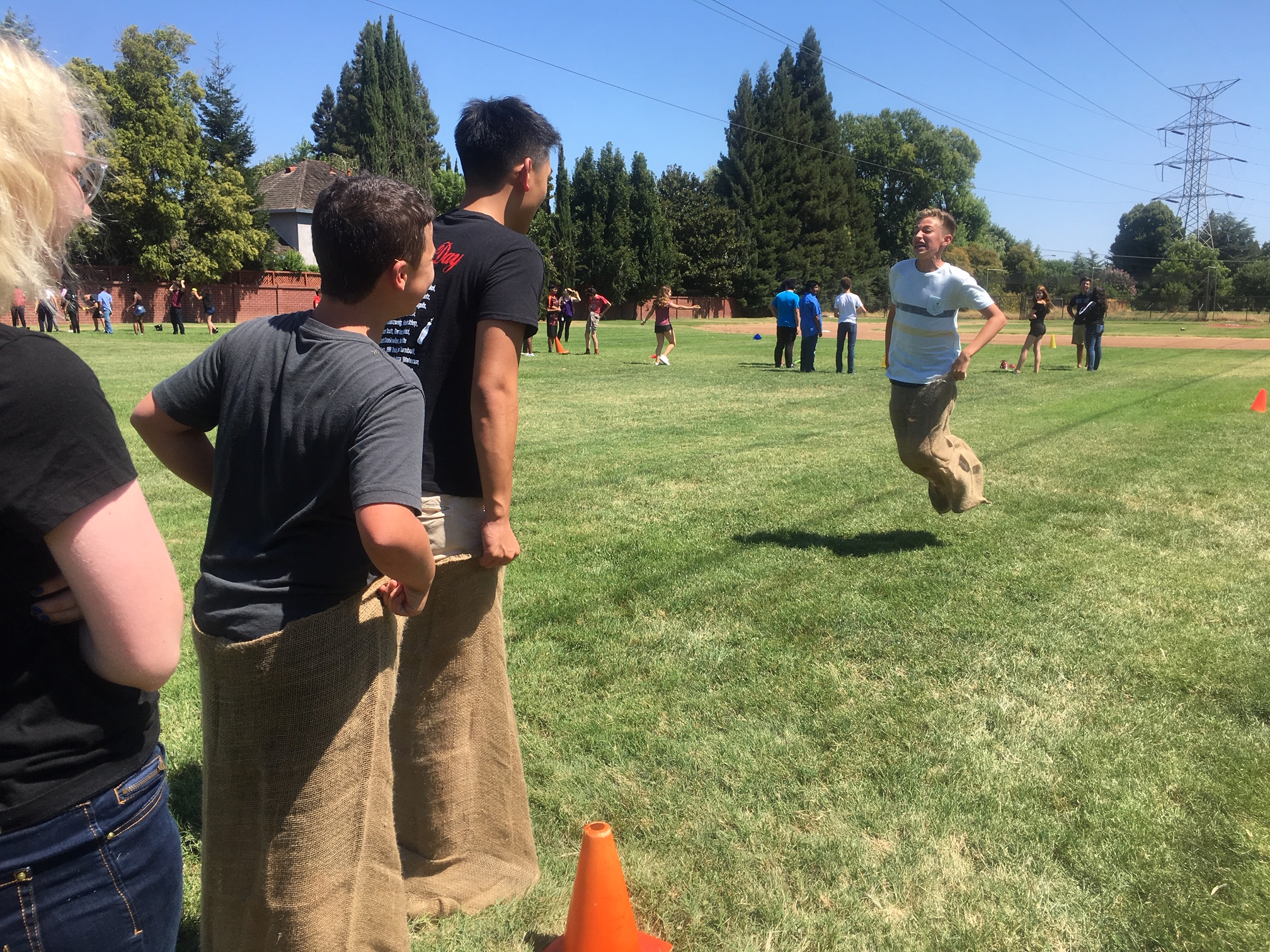 As teammate senior Jason Li (second from right) waits to take over in the sack race relay, freshman Ross Vargo jumps toward the finish. (Photo by Larkin Barnard-Bahn)