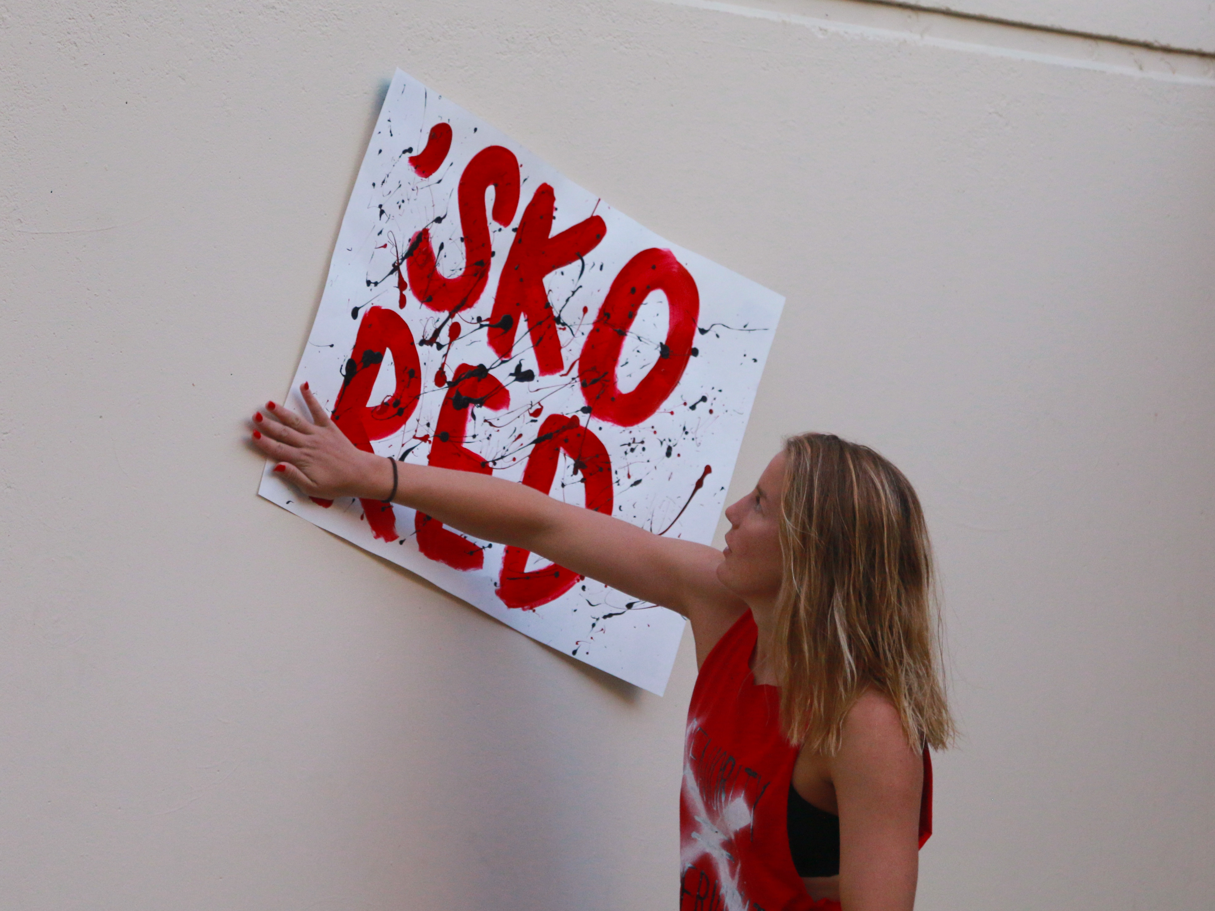 The morning of the game, junior Sydney Turner puts up Red Team decorations. (Photo by Hermione Xian)