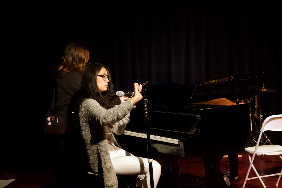 "Huynh Van adjusts the microphone before singing with and accompanying Whitney on the piano. The duo performed ""Dancing On My Own"" by Calum Scott. (Photo by Shimin Zhang)"
