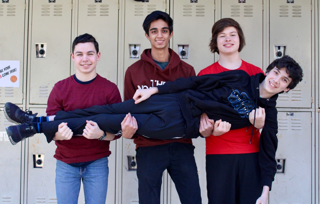Spreading Country Day spirit with their red and black apparel, sophomores Craig Bolman, Arijit Trivedi and Miles Morrow hold sophomore Dylan Margolis.