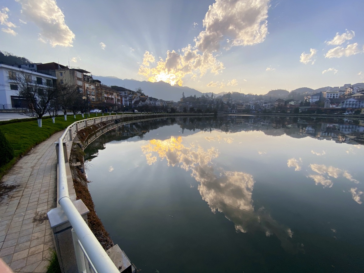 A view of the lake in Central Sapa showing the fansipan mountain in the background with the sun setting just behind it