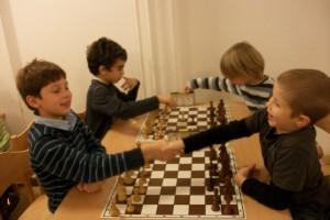 Während Can mit seinem Gegner bereits die ersten Züge austauschen, posieren vorne zwei Kinder. :-)