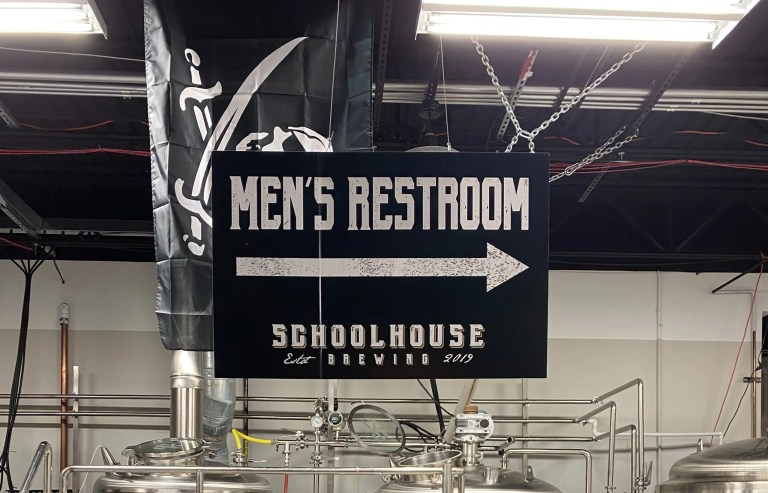 Directional sign pointing to the men's restroom, which no one seems to be able to find