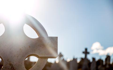Die Sonne blinzelt hinter einem Grabstein hervor, weitere Gräber im Hintergrund
