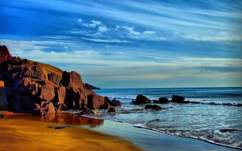 Strand, Klippen und Meer unter blauem Himmel