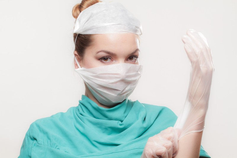 Doktorin zieht sich Handschuhe an