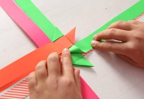 Beginnen Sie nun mit dem unteren rechten Streifen (hier grün) und drehen 90° nach rechts hinten eine Schlaufe.