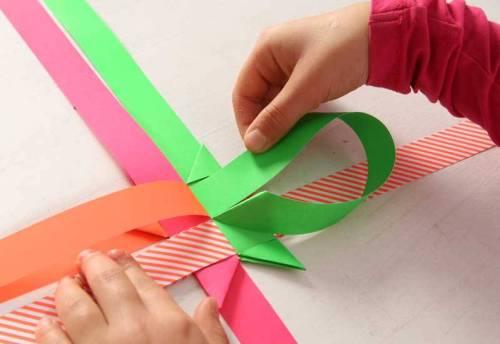 Stecken Sie ihn unter dem oberen, waagerechten Streifen (hier orange) durch und ziehen Ihn fest. So entsteht ein kleines Tütchen.