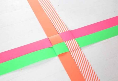 Der letzte Streifen wird zusätzlich durch die Schlaufe des zuerst geklappten Streifens gefädelt.