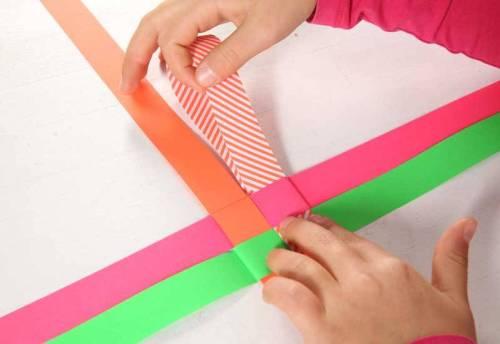 Klappen Sie jetzt das Dreieck nach hinten weg und fädeln den Streifen in die darunterliegende Schlaufe.