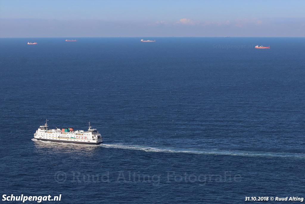 De veerboot Schulpengat passeert enkele schepen die voor anker liggen aan de rand van de Eurogeul bij Rotterdam.