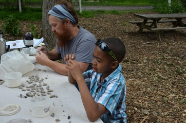 B. H. Mills and an attendee make clay bees at the Great American Backyard Campout