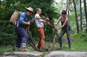 Volunteers work with WE THE WEEDS to weave vines