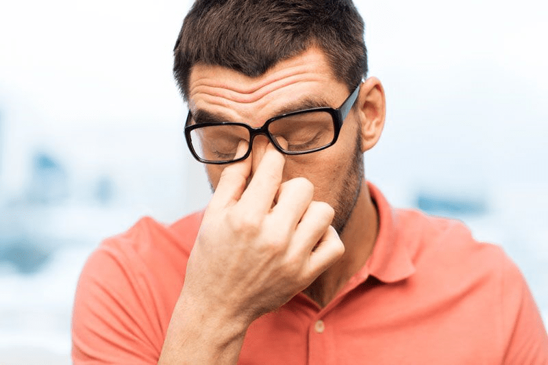 stressed man pinching the bridge of his nose