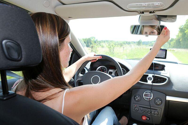 teen adjusting her rearview mirror