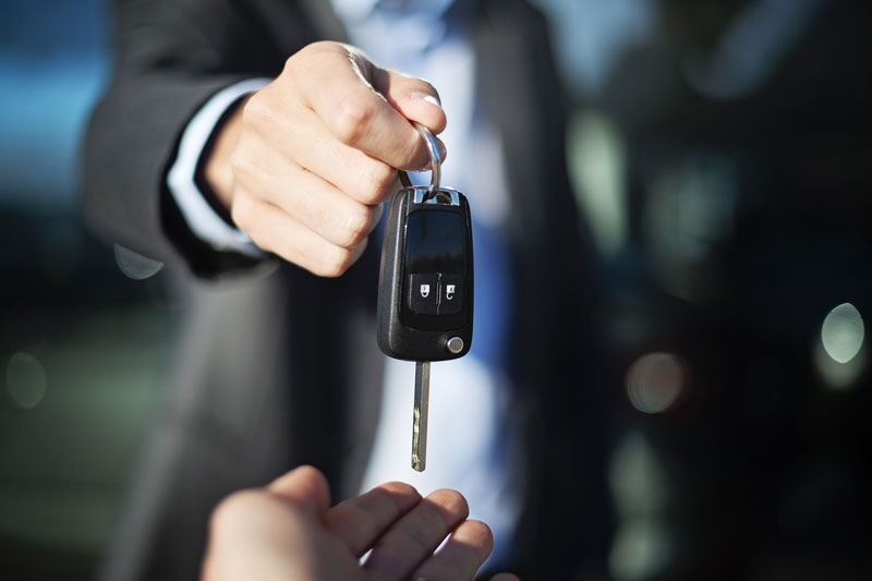 someone handing over keys to new car