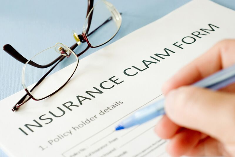 man completing insurance claim form
