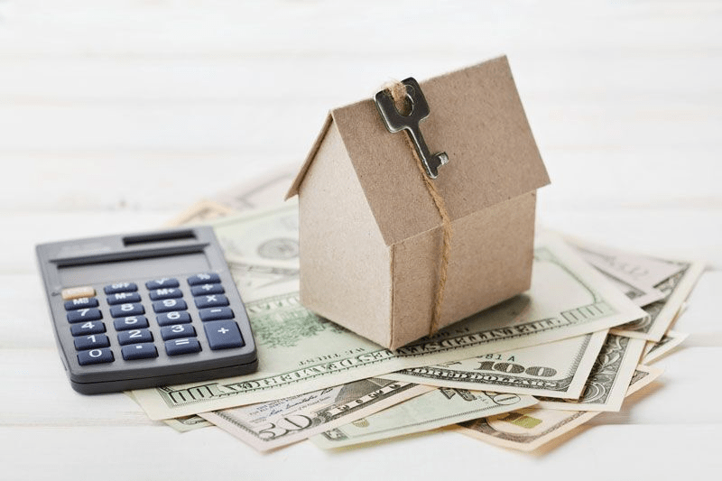 cardboard home next to calculator and money