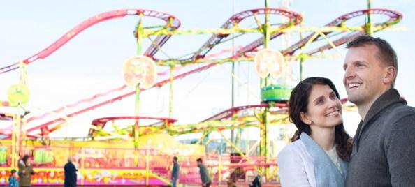 Vista panorâmica do casal lindo turista visitando parque de diversões colorido com montanha-russa passeio (MJTH) s