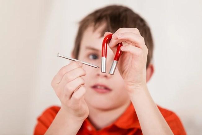 Foco seletivo close-up nas mãos do menino movendo um grande prego de ferro próximo ao ímã vermelho e branco (Jan H Andersen) S
