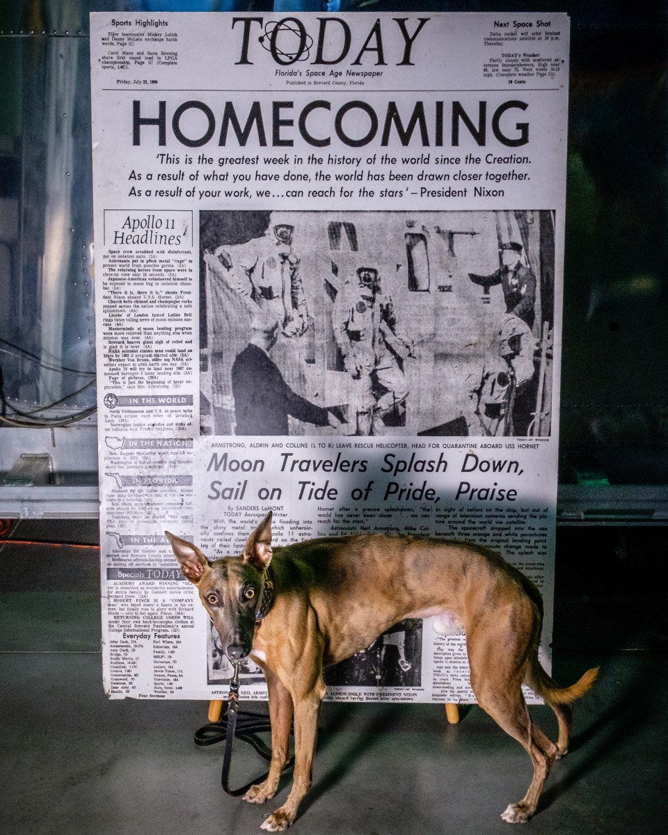 """Kuiper stands with an enlarged newspaper with the headline """"Today, Homecoming"""" and a picture of the Apollo 11 astronauts"""