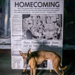 "Kuiper stands with an enlarged newspaper with the headline ""Today, Homecoming"" and a picture of the Apollo 11 astronauts"