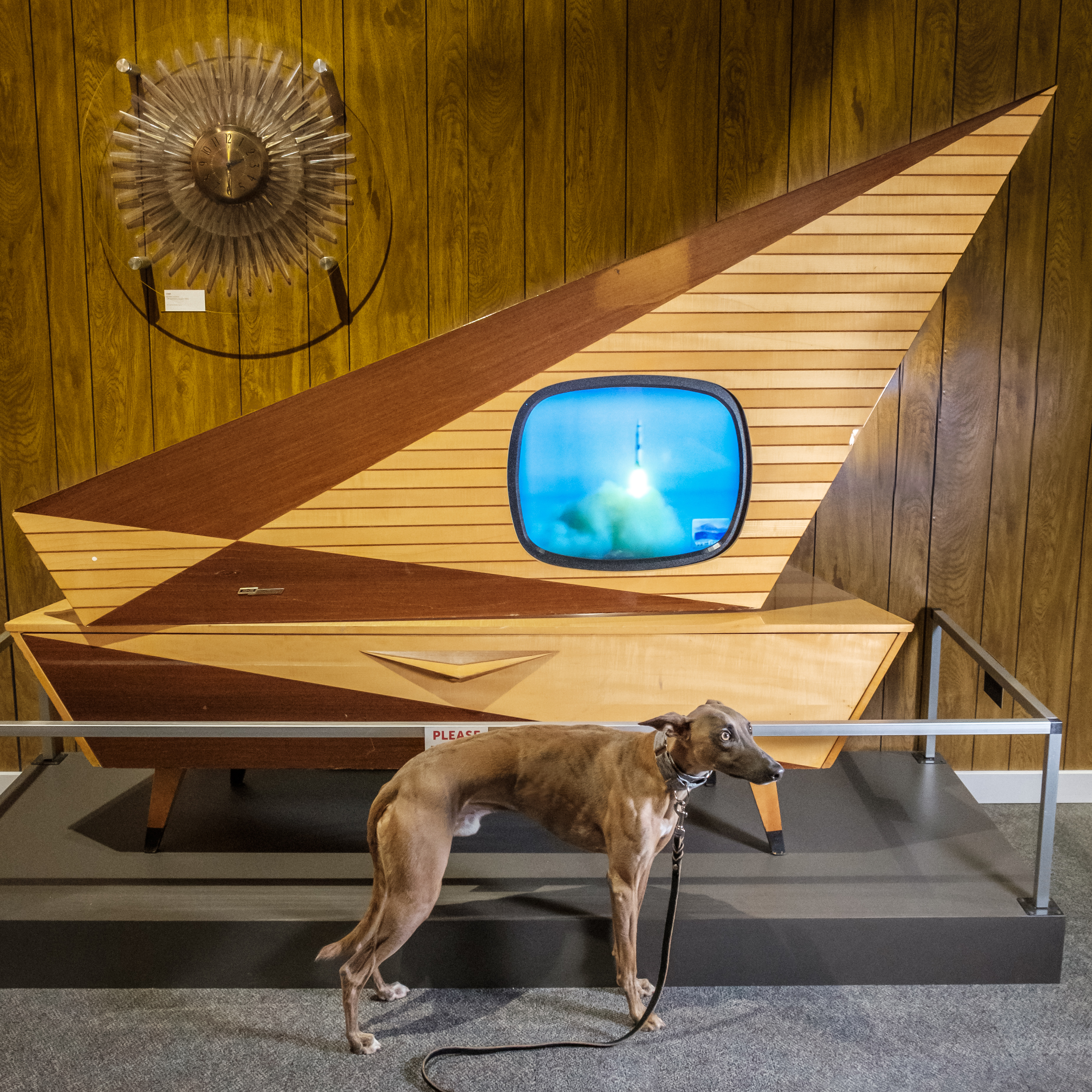 Kuiper poses with a large vintage triangle-shaped wooden TV. It is displaying a rocket launch.