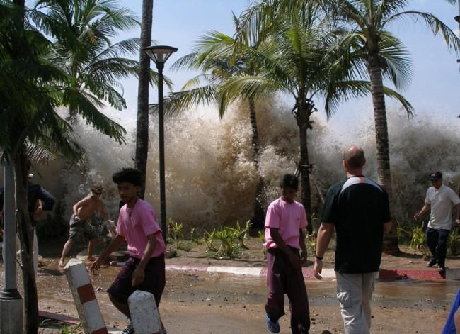 An incredible scene from the 2004 tsunami in Thailand has been captured in this memorable photo. As a huge wall of water bursts through the trees people begin to scatter in every direction, previously unaware of the danger that was so close by.