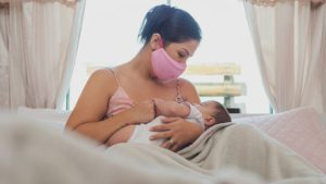 Mother nursing a child wearing a mask