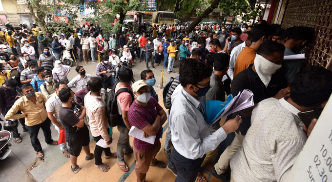 people waiting in lines outside a pharmacy in Pune
