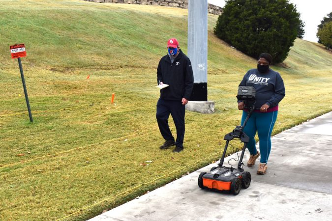 Scott Hammerstedt looks on while Alicia Odewale pushes a ground survey machine