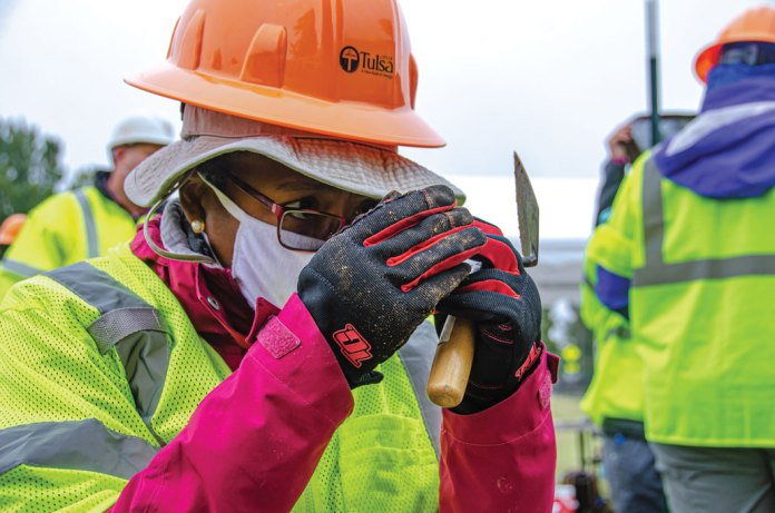 Phoebe Stubblefield looks closely at something in her hands while holding a trowel