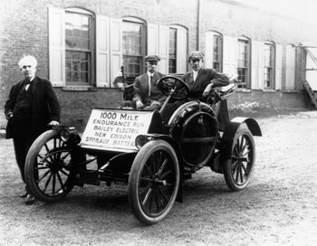 a black and white photo of Thomas Edison standing next to a car