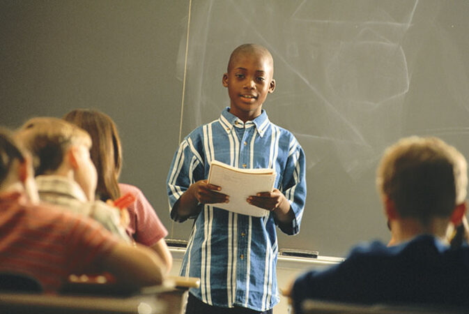 a boy gives a speeh in front of a classroom