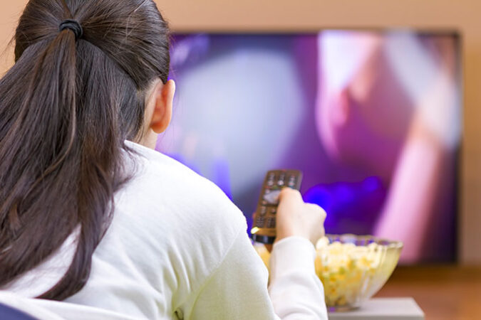 a photo of the back of the head of a girl watching TV with a bowl of popcorn